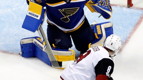 St. Louis Blues goalie Jake Allen, top, watches the puck as Arizona Coyotes' Tobias Rieder skates past during the second period of an NHL hockey game Monday, March 27, 2017, in St. Louis. (AP Photo/Jeff Roberson)