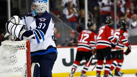Winnipeg Jets goalie Connor Hellebuyck (37) stands on his net as New Jersey Devils players celebrate a goal by Stefan Noesen (23) during the second period of an NHL game, Tuesday, March 28, 2017, in Newark, N.J. (AP Photo/Julio Cortez)