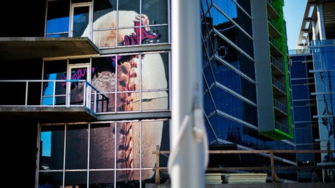 FILE - In this Thursday, March 9, 2017, file photo, a billboard of a baseball is reflected in the windows of hotel rooms under construction with a view into SunTrust Park, the Atlanta Braves' new baseball stadium in Atlanta. The team and its new SunTrust Park will share top billing in its 60-acre complex with The Battery Atlanta, the mixed-use development that will include restaurants, bars, shopping, apartments, a four-star hotel and a concert hall. The Braves believe their complex will be a model used when other teams look to build new parks. (AP Photo/David Goldman, File)