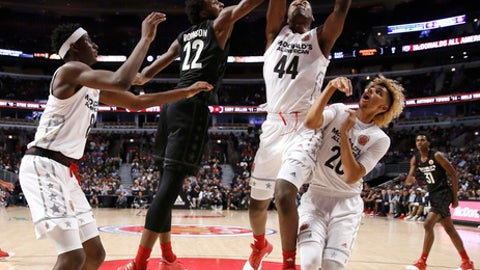 """Big East's Mitchell Robinson (22) blocks the shot of Big West's Brandon L. McCoy (44) as Jaren Jackson Jr., left, and Brian """"Tugs"""" Bowen II, watch during the second half of the McDonald's All-American boys basketball game Wednesday, March 29, 2017, in Chicago. The West team won 109-107. (AP Photo/Nam Y. Huh)"""
