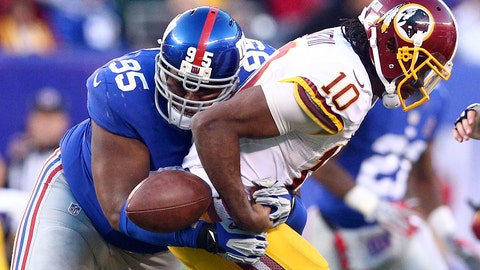 Dec 14, 2014; East Rutherford, NJ, USA; Washington Redskins quarterback Robert Griffin III (10) fumbles the ball as he's hit by New York Giants defensive tackle Johnathan Hankins (95) during the fourth quarter of a game at MetLife Stadium. Mandatory Credit: Brad Penner-USA TODAY Sports