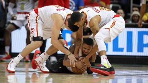 Mar 18, 2017; Atlanta, GA, USA; Portland Trail Blazers guard Damian Lillard (0) dives on a loose ball against Atlanta Hawks forward Ersan Ilyasova (7) and forward Thabo Sefolosha (25) in the second quarter of their game  at Philips Arena. Mandatory Credit: Jason Getz-USA TODAY Sports