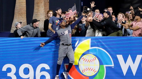 U.S. outfielder Adam Jones grabs a catch above the wall for the out on the Dominican Republic's Manny Machado during the seventh inning of a second-round World Baseball Classic baseball game Saturday, March 18, 2017, in San Diego. (AP Photo/Gregory Bull)
