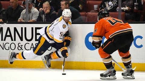 Nashville Predators left wing Austin Watson, left, passes the puck as Anaheim Ducks defenseman Sami Vatanen, of Finland, puts pressure on during the first period of an NHL hockey game, Tuesday, March 7, 2017, in Anaheim, Calif. (AP Photo/Mark J. Terrill)