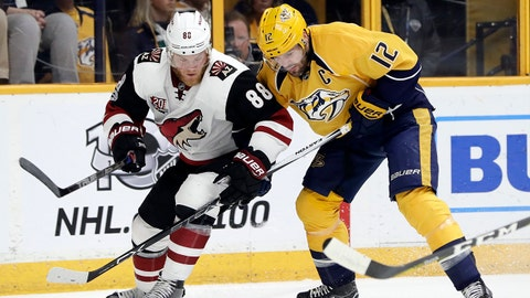 Arizona Coyotes left wing Jamie McGinn (88) and Nashville Predators center Mike Fisher (12) battle for the puck during the first period of an NHL hockey game Monday, March 20, 2017, in Nashville, Tenn. (AP Photo/Mark Humphrey)
