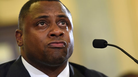 FILE - In this Dec. 2, 2014, file photo, National Football League (NFL) Executive Vice President of Football Operations Troy Vincent becomes emotional as he testifies on Capitol Hill in Washington, before the Senate Commerce Committee hearing on domestic violence in professional sports.  For Vincent, the bloody sights and bone-chilling sounds are as raw today as they were when he was an 8-year-old, huddling in a closet with his younger brother while his mother was being beaten by a boyfriend. Rather than repress those memories, the NFL's vice president of football operations is driven to share them.  (AP Photo/Susan Walsh, File)