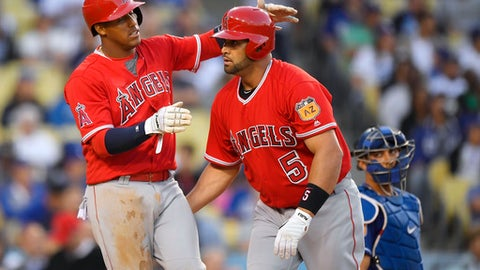 Los Angeles Angels' Albert Pujols, right, is congratulated by Yunel Escobar for a two-run home run, as Los Angeles Dodgers catcher Austin Barnes watches during the third inning of an exhibition baseball game, Saturday, April 1, 2017, in Los Angeles. (AP Photo/Mark J. Terrill)