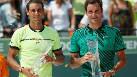 Rafael Nadal, of Spain, left, and Roger Federer, of Switzerland, hold their trophies as they pose for photos after the men's singles final tennis match at the Miami Open, Sunday, April 2, 2017, in Key Biscayne, Fla. Federer defeated Nadal. (AP Photo/Wilfredo Lee)