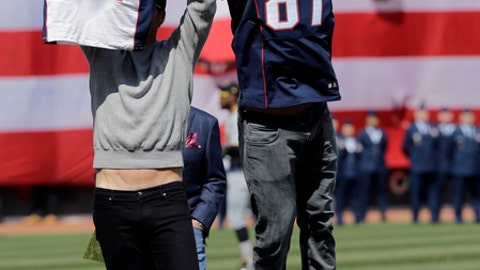 New England Patriots tight End Rob Gronkowski jumps to take quarterback Tom Brady's recovered Super Bowl jersey as he jokes around during baseball Boston Red Sox Home Opening Day ceremonies at Fenway Park, Monday, April 3, 2017, in Boston. The Red Sox face the Pittsburgh Pirates. (AP Photo/Elise Amendola).