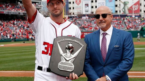 Washington Nationals starting pitcher Max Scherzer, left, waves after receiving the National League Cy Young Award from Washington Nationals general manager Mike Rizzo, before an opening day baseball game against the Miami Marlins, at Nationals Park, Monday, April 3, 2017, in Washington. (AP Photo/Alex Brandon)