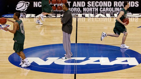 """FILE - In this March 18, 2009, file photo, Binghamton coach Kevin Broadus, center, looks on during a basketball practice for a first round NCAA college basketball game against Duke, in Greensboro, N.C.  The NCAA says it will consider North Carolina as a host for championship events again after the state rolled back a law that limited protections for LGBT people. In a statement Tuesday, April 4, 2017, the governing body said its Board of Governors had reviewed moves to repeal repealed the so-called """"bathroom bill"""" and replace it with a compromise law. (AP Photo/Steve Helber, File)"""