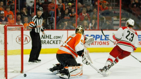 The puck rolls back out of the net after Carolina Hurricanes' Brock McGinn, right, scored past Philadelphia Flyers' Anthony Stolarz during the shootout of an NHL hockey game, Sunday, April 9, 2017, in Philadelphia. Carolina won 4-3. (AP Photo/Tom Mihalek)