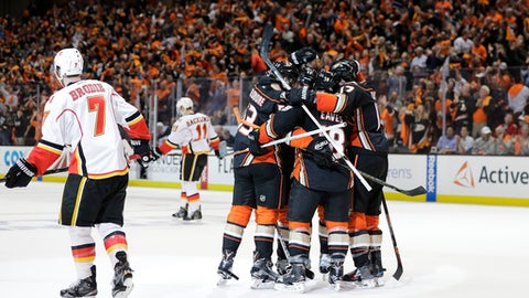 Anaheim Ducks players celebrate a goal by Jakob Silfverberg, of Sweden, as Calgary Flames' T.J. Brodie, left, and Mikael Backlund, of Sweden, skate away during the second period in Game 1 of a first-round NHL hockey Stanley Cup playoff series Thursday, April 13, 2017, in Anaheim, Calif. (AP Photo/Jae C. Hong)