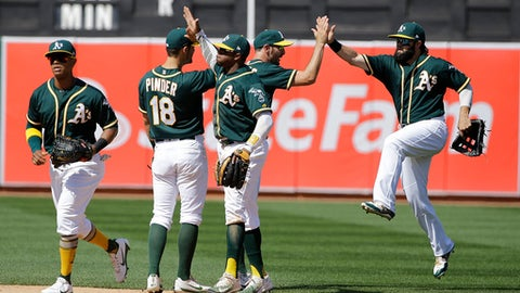 Oakland Athletics' Khris Davis heads away as Chad Pinder, Rajai Davis, Adam Rosales and Jaff Decker, from second from left, celebrates after the team's baseball game against the Texas Rangers in Oakland, Calif., Wednesday, April 19, 2017. The Athletics won 9-1. (AP Photo/Jeff Chiu)