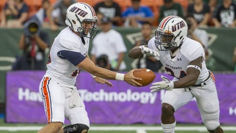 Tennessee-Martin quarterback Troy Cook, left, hands off the football to running back Jaimiee Bowe (24) during the first quarter of an NCAA college football game against Hawaii, Saturday, Sept. 10, 2016, in Honolulu. (AP Photo/Eugene Tanner)