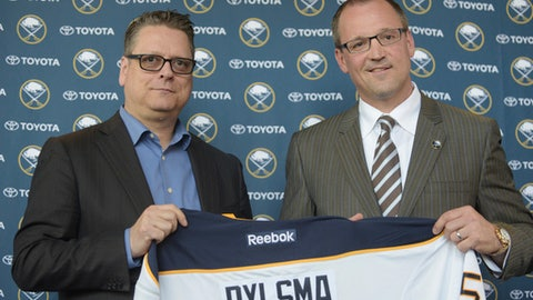 FILE - In this May 28, 2015, file photo, Buffalo Sabres GM Tim Murray, left, and newly hired coach Dan Bylsma hold a Sabres' jersey as they pose for a photo after a news conference in Buffalo, N.Y.  The Sabres have fired general manager Tim Murray and coach Dan Bylsma after the youthful team missed the playoffs for a sixth consecutive season. Owner Terry Pegula made the announcement Thursday, April 20, 2017. (AP Photo/Gary Wiepert, File)