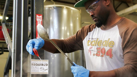 In this Feb. 16, 2017, photo provided by AleSmith, Tony Gwynn Jr. wears safety goggles as he waits for the right moment to add hops to a boil kettle as he tweaks his craft beer recipe on a two-keg system dwarfed by giant tanks at AleSmith Brewing Co. in San Diego, Calif. Gwynn followed in the footsteps of his famous father in playing at San Diego State and even with the Padres, and now he hopes to hit on something similar to San Diego Pale Ale .394, AleSmith's tribute to the late Hall of Famer. (Elvin Piring/AleSmith via AP)