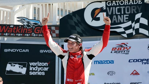 "FILE - In this Sept. 3, 2016, file photo, Zach Veach (5) celebrates in Victory Lane after winning an Indy Lights auto race at The Glen in Watkins Glen, N.Y.  Veach plans to take this weekend ""step by step"" and progress ""very methodically."" If it doesn't sound like the typical weekend agenda for a 22-year-old, well, Veach isn't the typical 22-year-old. He'll make his IndyCar debut at Barber Motorsports Park Sunday. (AP Photo/Mel Evans, File)"