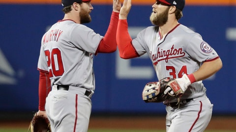 Washington Nationals' Bryce Harper (34) and Daniel Murphy (20) celebrate after a baseball game against the New York Mets, Friday, April 21, 2017, in New York. (AP Photo/Frank Franklin II)