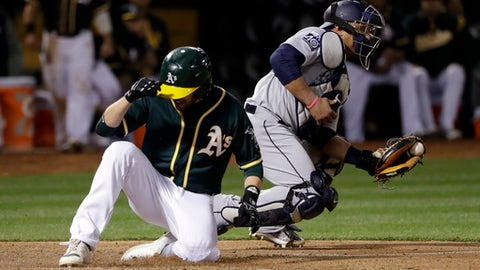 Oakland Athletics' Jed Lowrie scores past Seattle Mariners catcher Carlos Ruiz on a sacrifice fly by Stephen Vogt during the sixth inning a baseball game Friday, April 21, 2017, in Oakland, Calif. (AP Photo/Marcio Jose Sanchez)