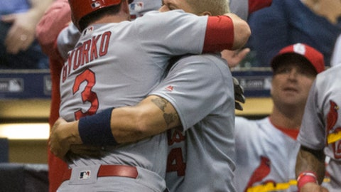 St. Louis Cardinals' Jedd Gyorko is hugged by Yadier Molina after hitting a triple and then scoring on a throwing error during the ninth inning of a baseball game Saturday, April 22, 2017, in Milwaukee. (AP Photo/Tom Lynn)