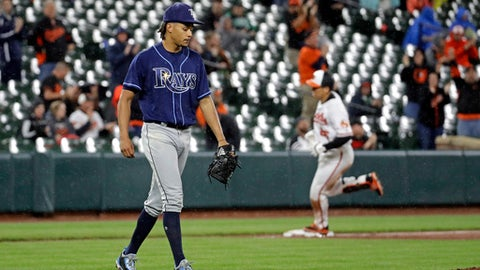 Tampa Bay Rays starting pitcher Chris Archer, left, walks on the field as Baltimore Orioles' Hyun Soo Kim, back right, of South Korea, rounds the bases after hitting a solo home run in the sixth inning of a baseball game in Baltimore, Monday, April 24, 2017. (AP Photo/Patrick Semansky)