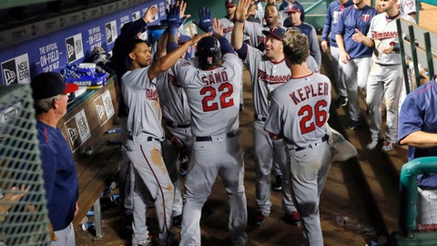 The Minnesota Twins dugout celebrates with Miguel Sano (22) following Sano's solo home run off of Texas Rangers starting pitcher Andrew Cashner during the fifth inning of a baseball game in Arlington, Texas, Tuesday, April 25, 2017. (AP Photo/Tony Gutierrez)