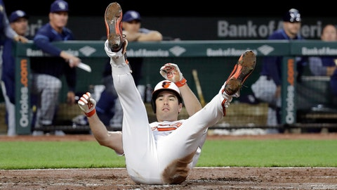 Baltimore Orioles' Seth Smith rolls over after safely crossing home plate on a single that was extended after a pair of throwing errors in the second inning of a baseball game against the Tampa Bay Rays in Baltimore, Wednesday, April 26, 2017. (AP Photo/Patrick Semansky)