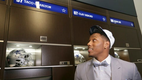 The Dallas Cowboys' No. 1 draft pick, defensive end Taco Charlton, looks at his new locker at the team's football headquarters in Frisco, Texas, Friday, April 28, 2017. (AP Photo/LM Otero)