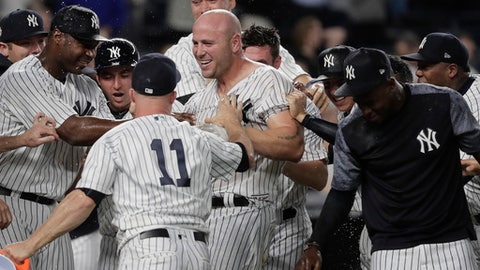 New York Yankees left fielder Matt Holliday, center, celebrates with teammates after hitting a three-run home run to beat the Baltimore Orioles during the tenth inning of a baseball game, Friday, April 28, 2017, in New York. (AP Photo/Julie Jacobson)