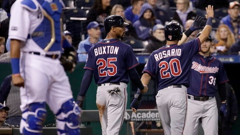 Minnesota Twins' Byron Buxton (25) and Eddie Rosario (20) walk back to the dugout after scoring on a double by Miguel Sano during the eighth inning of a baseball game against the Kansas City Royals Friday, April 28, 2017, in Kansas City, Mo. (AP Photo/Charlie Riedel)