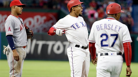 Los Angeles Angels third baseman Yunel Escobar, left, and Texas Rangers third base coach Tony Beasley (27) watch as Rangers' Carlos Gomez, center, celebrates his triple off Angels starter Jesse Chavez during the fifth inning of a baseball game in Arlington, Texas, Saturday, April 29, 2017. (AP Photo/Tony Gutierrez)