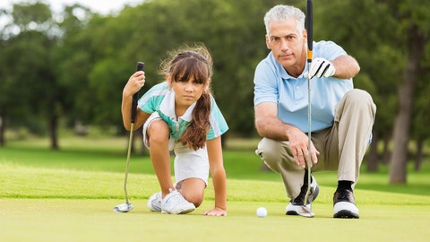 Senior adult Caucasian man is golf pro at country club. He is giving private golf lesson to elementary age Hispanic little girl. He is teaching student how to line up golf ball with putter on green course.
