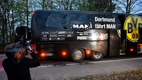 A camera man films Dortmund's team bus after it was damaged in an explosion before the Champions League quarterfinal soccer match between Borussia Dortmund and AS Monaco in Dortmund, western Germany, Tuesday, April 11, 2017.  (AP Photo/Martin Meissner)