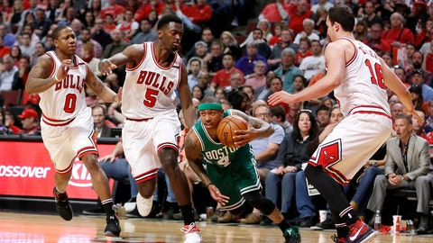 Boston Celtics' Isaiah Thomas (4) dribbles through the Chicago Bulls defense of Isaiah Canaan (0) Bobby Portis (5) and Paul Zipser during the first half in Game 4 of an NBA basketball first-round playoff series in Chicago, Sunday, April 23, 2017. (AP Photo/Charles Rex Arbogast)