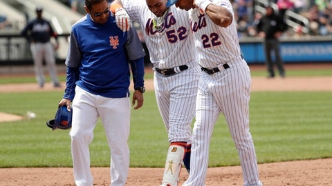 ADDS THE NAME OF THE TRAINER - New York Mets' Yoenis Cespedes (52) is helped off the field by first base coach Tom Goodwin (22) and  head athletic trainer Ray Ramirez during the fourth inning of a baseball game against the Atlanta Braves, Thursday, April 27, 2017, in New York. (AP Photo/Frank Franklin II)
