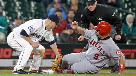 Los Angeles Angels' Albert Pujols (5) slides safely into third base on a stolen base as Seattle Mariners third baseman Kyle Seager puts on a late tag in the 11th inning of a baseball game Tuesday, May 2, 2017, in Seattle. Umpire Tom Woodring looks on. (AP Photo/Elaine Thompson)