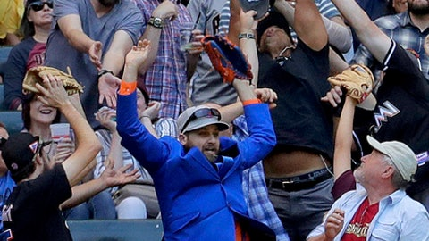 Fans reach for Arizona Diamondbacks Jake Lamb's two run home run against the New York Mets during the third inning of a baseball game, Wednesday, May 17, 2017, in Phoenix. (AP Photo/Matt York)
