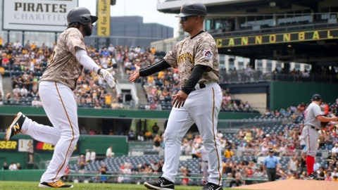 Pittsburgh Pirates' Josh Bell, left, is greeted by third base coach Joey Cora, center, after hitting a two-run home run off Washington Nationals starting pitcher Tanner Roark, right, in the first inning of a baseball game, Thursday, May 18, 2017, in Pittsburgh. (AP Photo/Keith Srakocic)