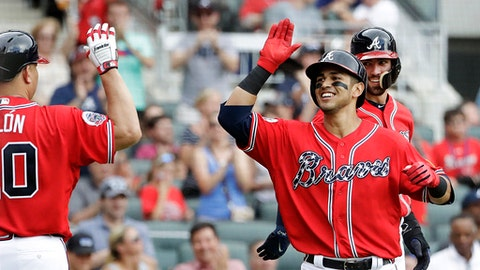 Atlanta Braves' Rio Ruiz, front right, high-fives Bartolo Colon, left, after hitting a two-run home run to also score Dansby Swanson, rear, in the second inning of a baseball game against the Washington Nationals in Atlanta, Saturday, May 20, 2017. (AP Photo/David Goldman)