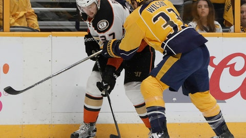 Anaheim Ducks left wing Nick Ritchie (37) is checked against the boards by Nashville Predators left wing Colin Wilson (33) during the first period in Game 6 of the Western Conference final in the NHL hockey Stanley Cup playoffs Monday, May 22, 2017, in Nashville, Tenn. (AP Photo/Mark Humphrey)