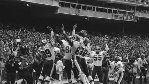 FILE - In this Jan. 8, 1983, file photo, members of the Washington Redskins celebrate after Alvin Garrett (89) scored against the Detroit Lions, in Washington. Also shown are Charlie Brown (87), Clarence Harmon (38) and Tom Turnure (55). The NFL wants to put some flair back into celebrations, allowing players to use the football as a prop, celebrate as a group and roll around on the ground again if they choose. (AP Photo/File)
