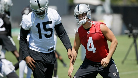 Oakland Raiders quarterback Derek Carr (4) stretches by wide receiver Michael Crabtree, (15) during an NFL football team activity Tuesday, May 23, 2017, in Alameda, Calif. (AP Photo/Eric Risberg)