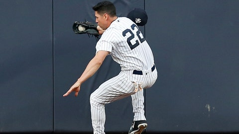 New York Yankees center fielder Jacoby Ellsbury (22) steadies himself after colliding with the outfield wall fielding a flyout hit by Kansas City Royals' Alcides Escobar during the first inning of a baseball game at Yankee Stadium in New York, Wednesday, May 24, 2017. Ellsbury left the game after the collision. (AP Photo/Kathy Willens)