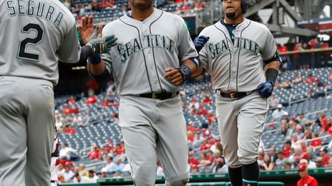 Seattle Mariners Nelson Cruz, right, runs back to the dugout with teammates Jean Segura (2) and Robinson Cano, center, after hitting a three-run home run with both Segura and Cano scoring during the sixth inning of a baseball game against the Washington Nationals in Washington, Thursday, May 25, 2017. The Mariners won 4-2. (AP Photo/Manuel Balce Ceneta)