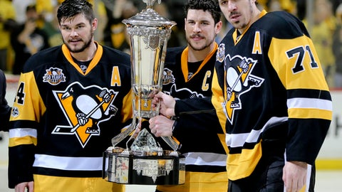 Pittsburgh Penguins' team captain Sidney Crosby (87) holds the Prince of Wales Trophy and poses with assistant captains Evgeni Malkin (71) and Chris Kunitz (14) after defeating the Ottawa Senators in Game 7 of the NHL hockey Stanley Cup Eastern Conference finals to advance to the Stanley Cup finals, Thursday, May 25, 2017, in Pittsburgh. The Penguins won 3-2 in double overtime. (AP Photo/Keith Srakocic)