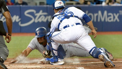 Toronto Blue Jays' catcher Russell Martin, right, tags out Texas Rangers' Elvis Andrus at home plate during third-inning baseball game action in Toronto, Friday, May 26, 2017. (Jon Blacker/The Canadian Press via AP)