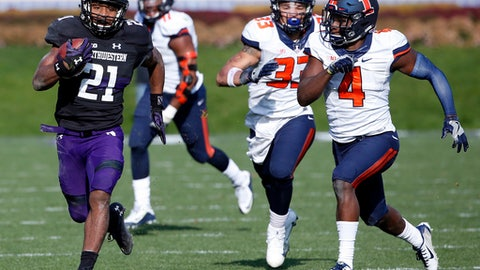 FILE - In this Nov. 26, 2016, file photo, Northwestern running back Justin Jackson, left, runs with the ball past Illinois defensive back Darwyn Kelly, right, and linebacker Tre Watson during the first half of an NCAA college football game in Evanston, Ill. Over the last three seasons, no Power Five team has relied on a running back as much as Northwestern has relied on Jackson, an old-school workhorse at a time of tailback-by-committee and early NFL draft entrants. (AP Photo/Nam Y. Huh, File)