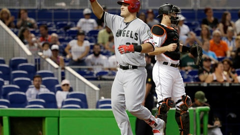 Los Angeles Angels' Mike Trout, left, crosses the plate past Miami Marlins catcher J.T. Realmuto to score on a solo home run during the first inning of an interleague baseball game, Saturday, May 27, 2017, in Miami. (AP Photo/Lynne Sladky)