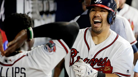 FILE - In this Friday, May 19, 2017, file photo, Atlanta Braves' Kurt Suzuki, right, celebrates with teammate Brandon Phillips after hitting a two-run home run in the eighth inning of a baseball game against the Washington Nationals in Atlanta. Suzuki had three passed balls in his first game catching knuckleballer R.A. Dickey for Atlanta this season but committed just one in Dickey's next eight starts. (AP Photo/David Goldman, File)